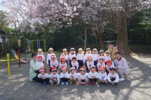 園庭の桜の前で、みんな揃って記念撮影(*^^*)お兄さん・お姉さんになりましたね♪の様子